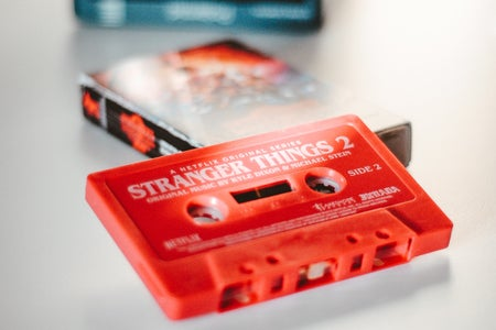 """A red cassette sits on a table labeled """"stranger things"""""""
