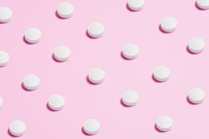 white pills placed on pink backdrop