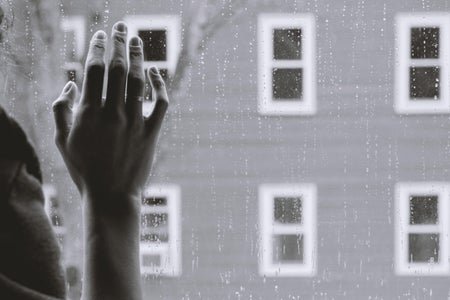Woman's hand against window on rainy day