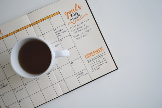 white ceramic mug with coffee on top of a bullet journal
