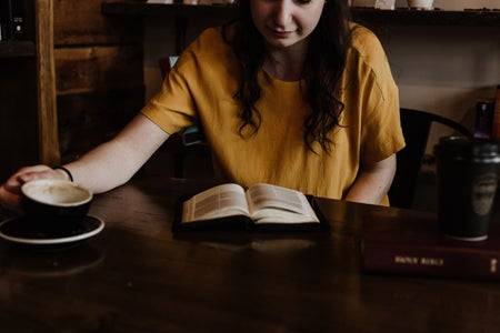 women sitting on a chair in front of book with coffee