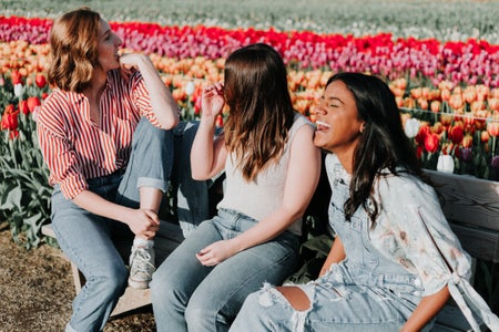 Three women talking and laughing on the wooden bench next to the tulip flower field