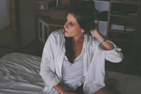 Girl sitting on bed alone