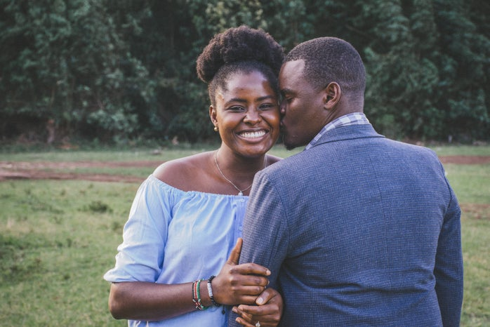 A black couple poses for the camera smiling