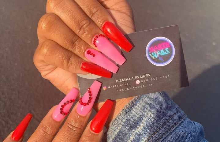 manicured hand holding business card