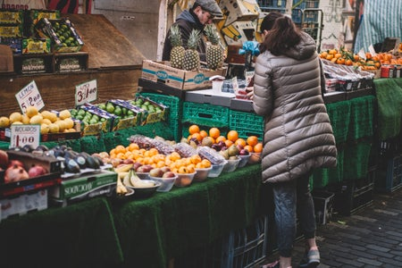 a woman shopping at a farmer's market fruit stall