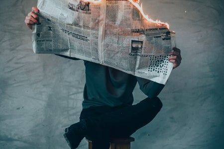 Man sitting with leg crossed reading a newspaper that is on fire.