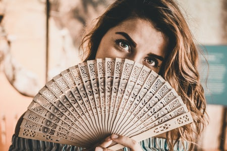 Woman holding a fan over her face