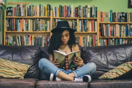 woman reading a book on a couch in a library