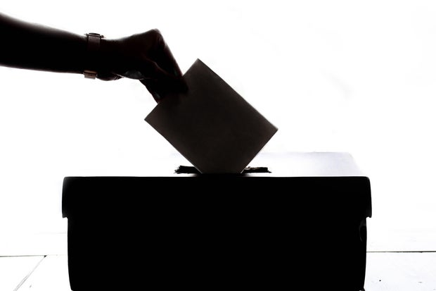 Black and white image of person putting ballot in box