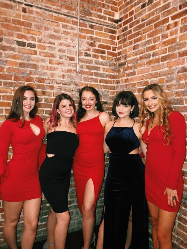 five women in black and red dresses standing in front of a brick wall