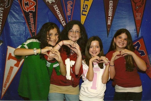 girls wearing sports team shirts holding up hand hearts