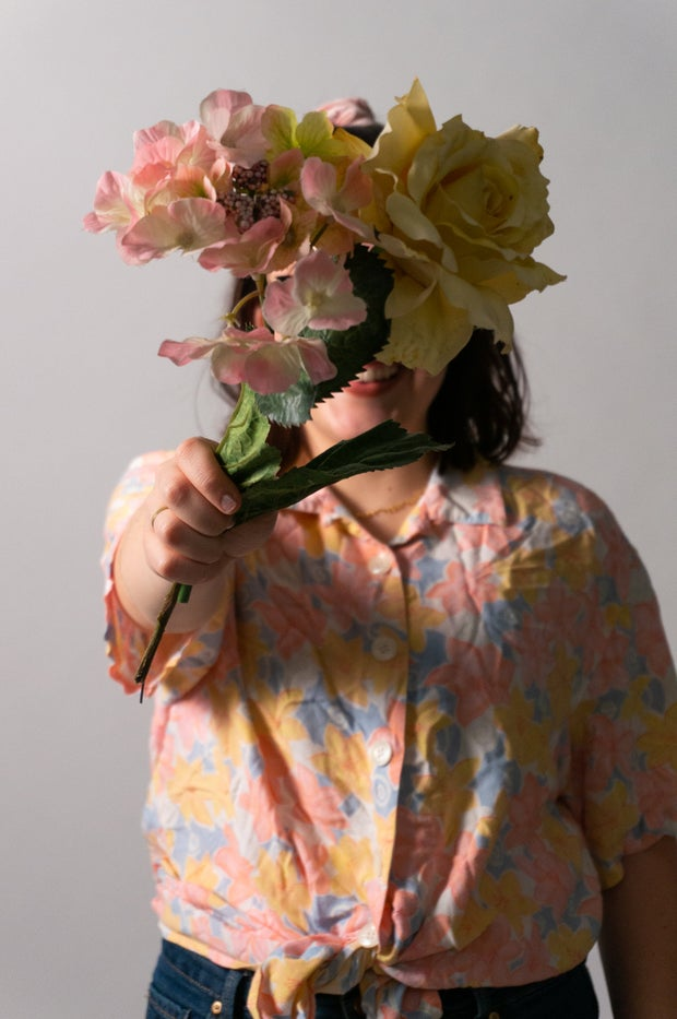 woman model wearing short sleeve blouse and holding flowers