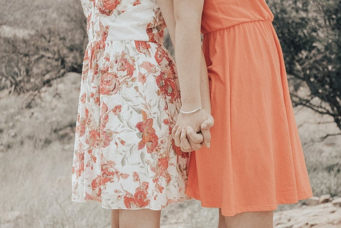My sister and I taking pictures outside, holding hands.