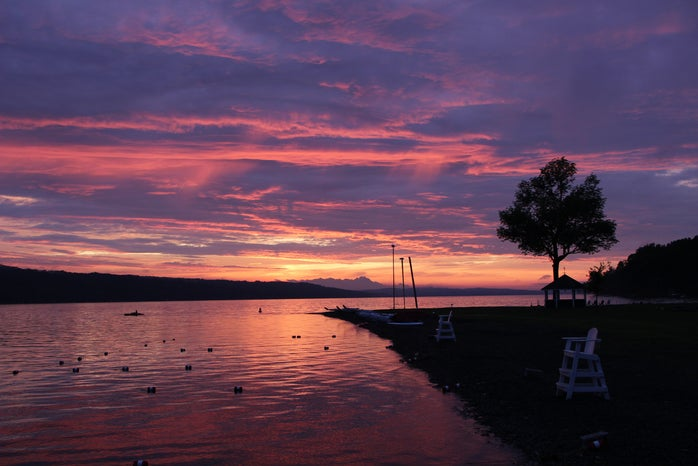 THE WATERFRONT AREA OF MY SUMMERCAMP WITH A PURPLE, PINK, BLUE AND GRAY CLOUDY SKY.