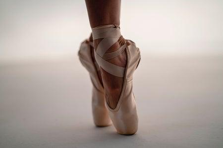 A ballerina on tip-toe in ballet slippers.