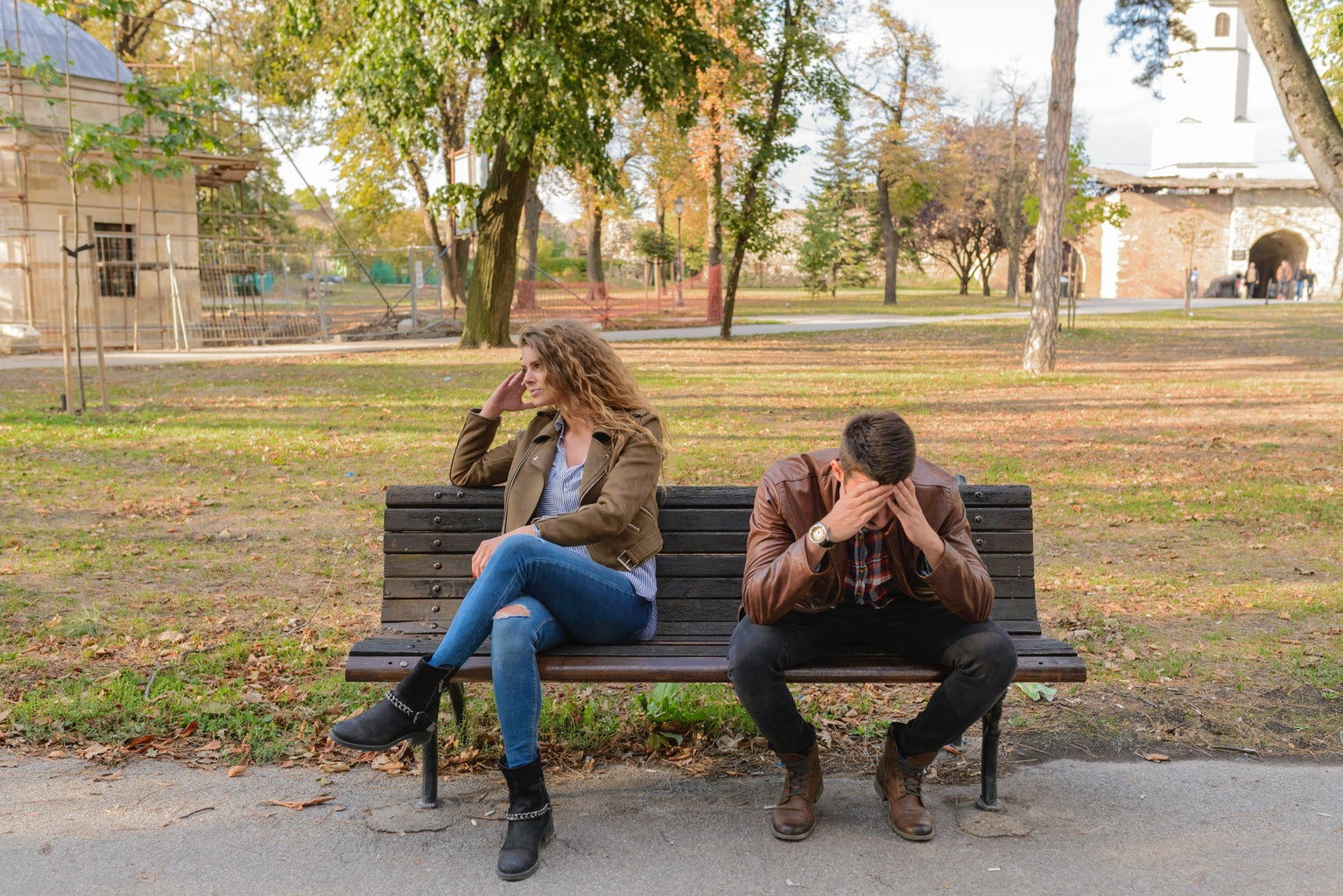 a man and a woman sit on a park bench looking frustrated