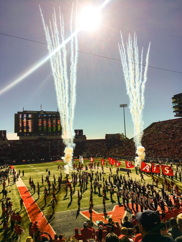 people standing at a stadium and a band marching