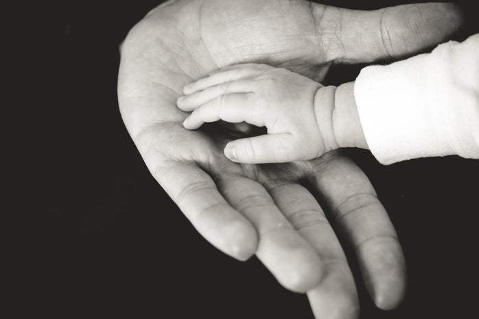 A baby\'s hand resting in the hand of their parent