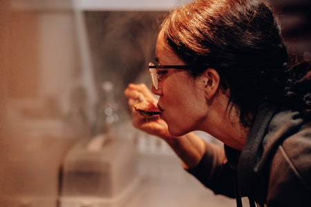 a woman leans over a pan of food, taste-testing it