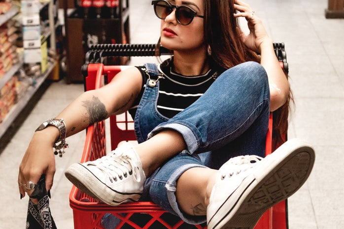 a woman sits in a red shopping cart in the middle of a store