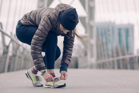 person kneels to tie their running shoes. they are wearing a coat and a hat and appear to be on a bridge