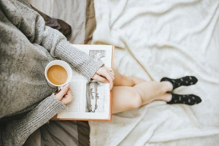 person sitting at the edge of a bed with an open book in their lap and a cup of coffee in hand