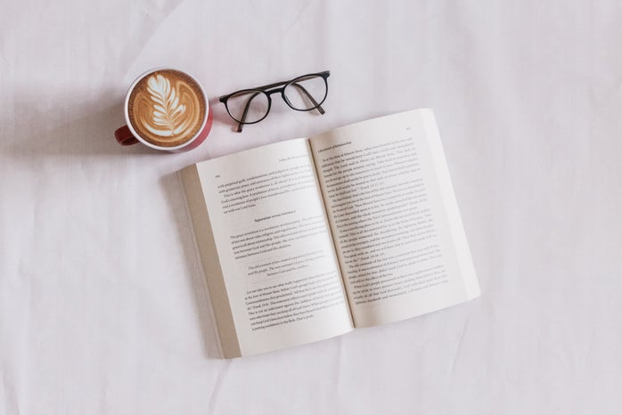open book with a cup of coffee and glasses