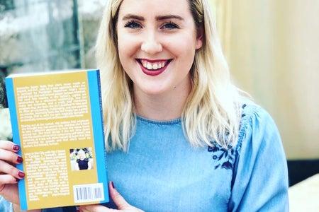 Caroline Trussell holding her novel