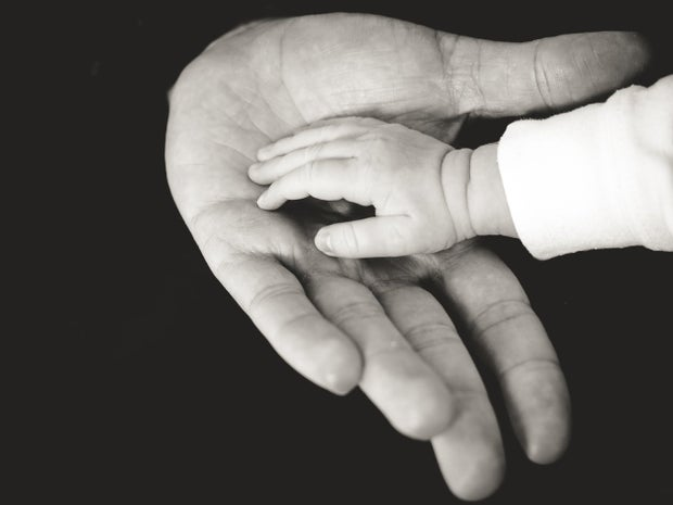 A baby's hand resting in the hand of their parent