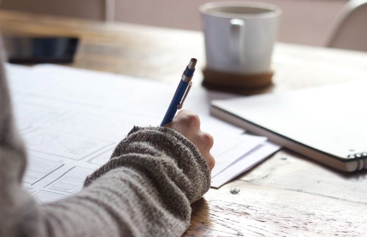 person writing in notebook with coffee cup