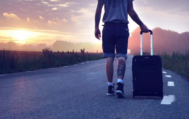 man with suitcase walking in sunset