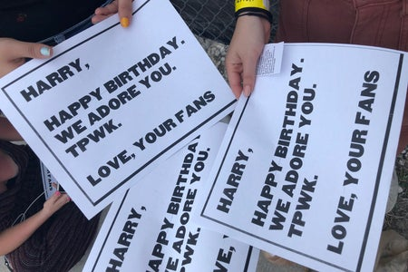 """Women holding signs that say """"Happy Birthday Harry"""" at a Harry Styles concert"""