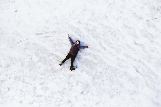 person laying in the snow