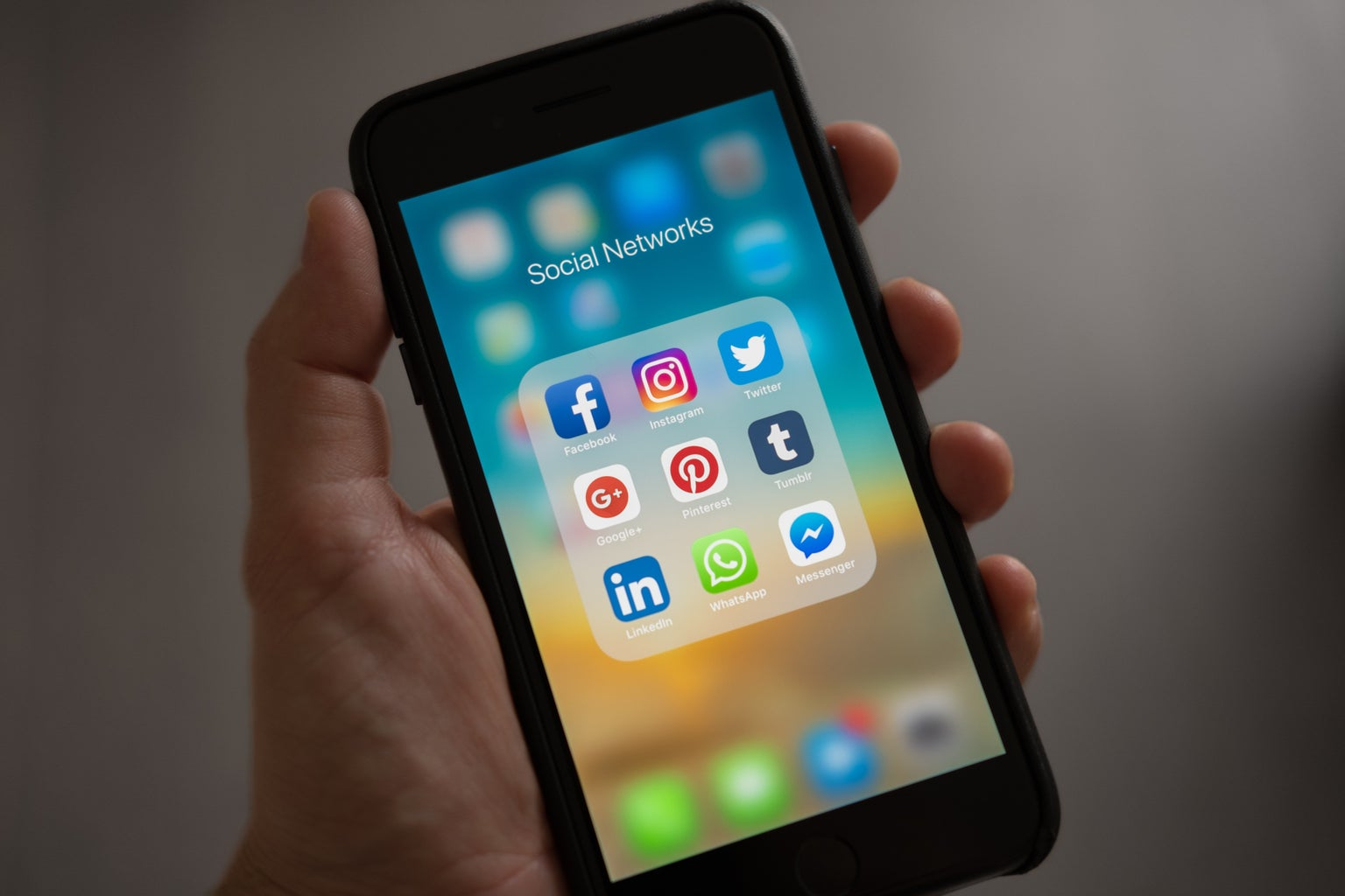 hand holding cell phone with social media apps open