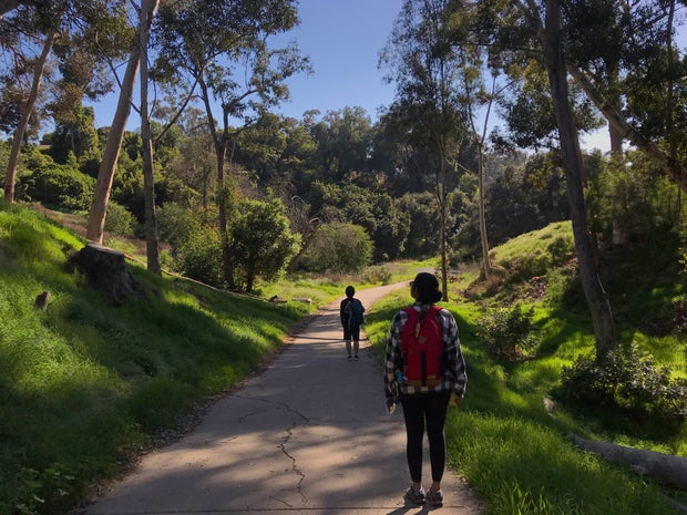 two people standing on a trail (spaced apart) with green trees all around them; the person closest to the camera has a red backpack