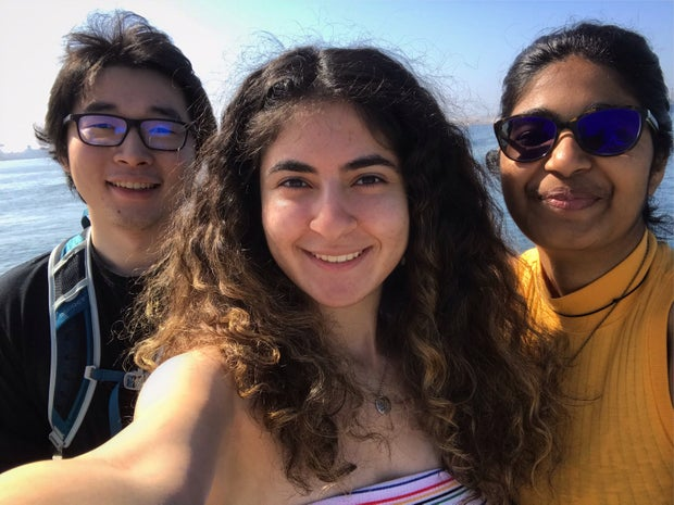 a selfie of three friends; the girl on the right has a yellow shirt