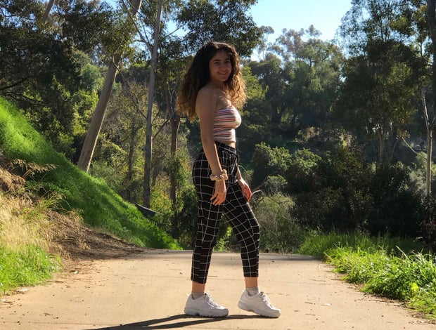 girl standing on a path with green trees around her; she is wearing grid pants and a striped tube top