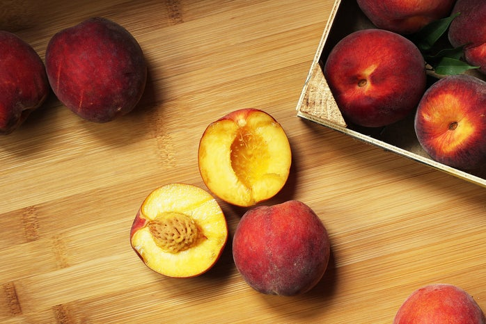 A halved peach sits on a table near other whole peaches.