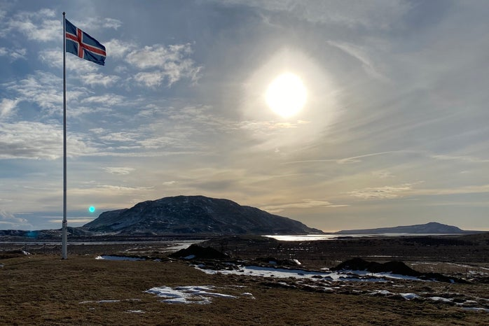 Icelandic flag with scenic background
