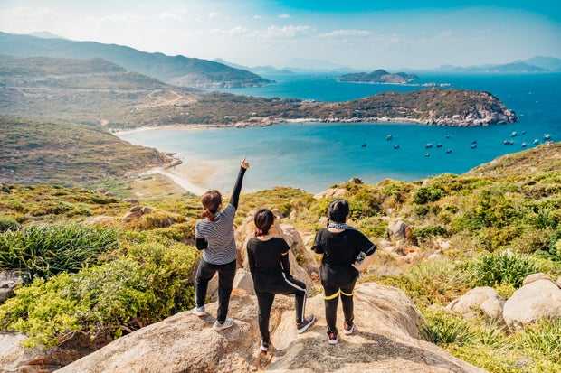 three women standing on the top of a cliff looking down on the water
