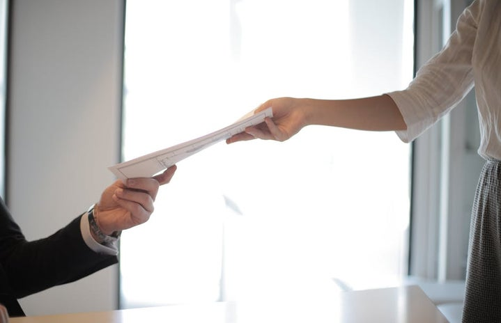 job applicant handing her documents and resume to employer during interview