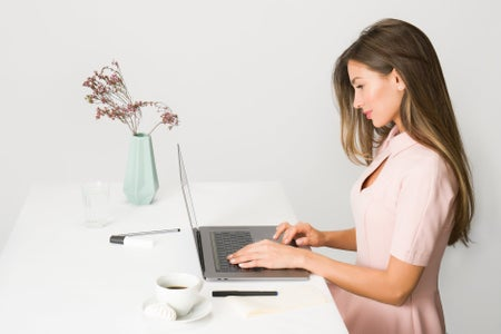 woman in pink dress working on laptop