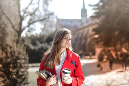 woman in red coat business casual holding books and a coffee