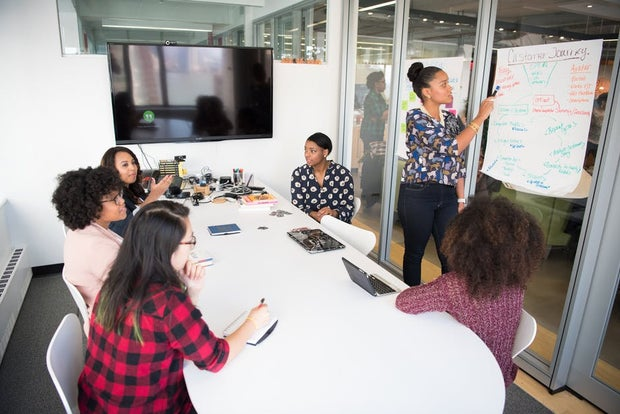 6 women working together in conference room meeting