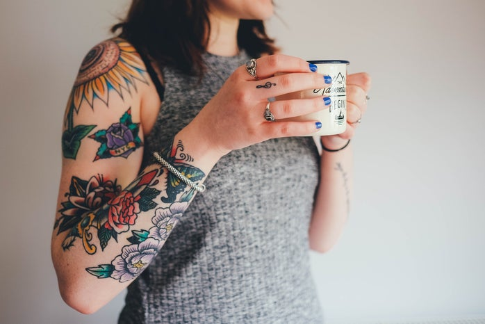 Woman with tattoos holding a mug