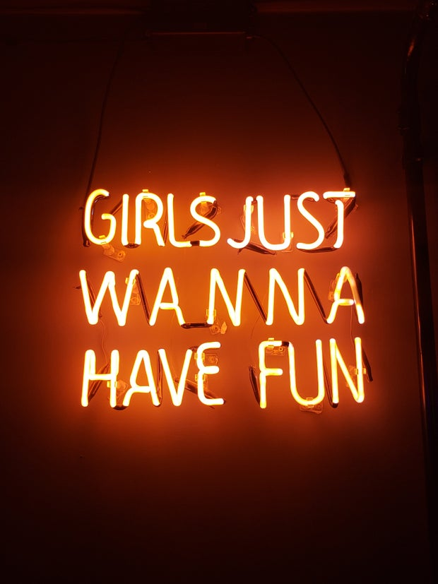 "Neon lights that spell out ""Girls Just Wanna Have Fun."""