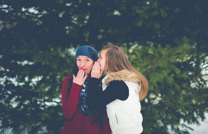 Woman whispering into other woman's ear