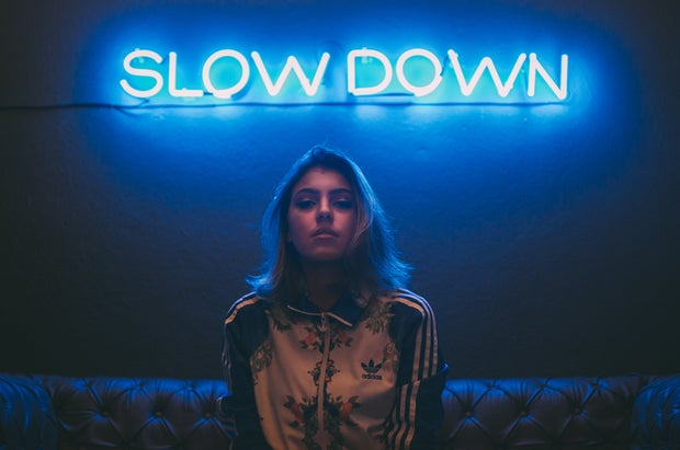 woman sitting on a brown sofa in front of a neon sign that says