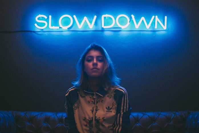 """woman sitting on a brown sofa in front of a neon sign that says """"slow down"""""""